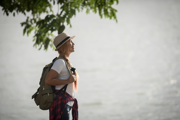 Young happy woman with backpack standing looking to the river. Free Photo