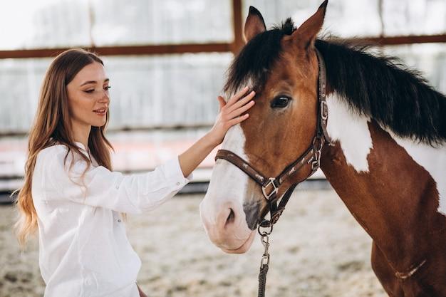 Молодая счастливая женщина с лошадью на ранчо Бесплатные Фотографии
