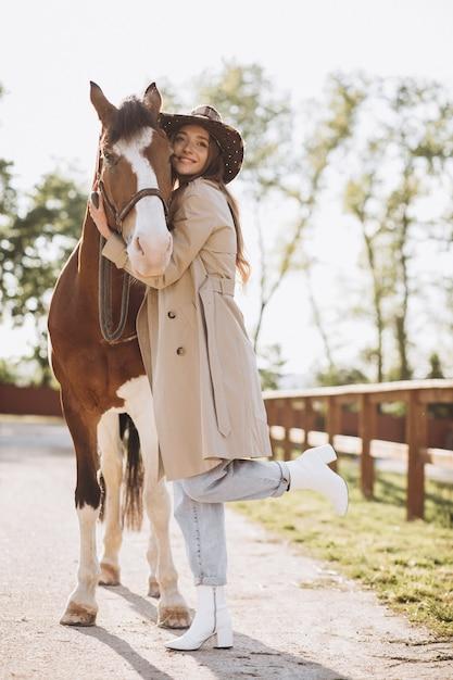 牧場で馬を持つ若い幸せな女 無料写真