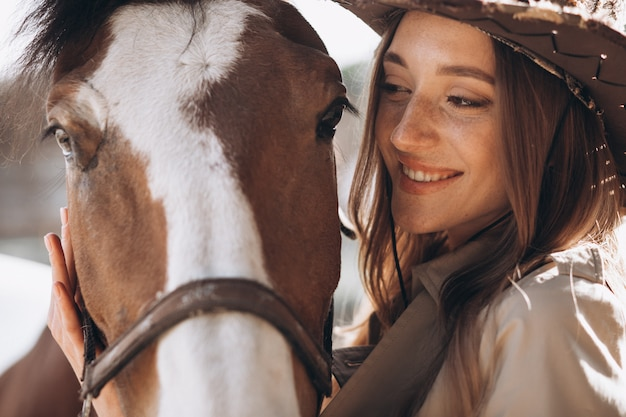 Young happy woman with horse at ranch Free Photo
