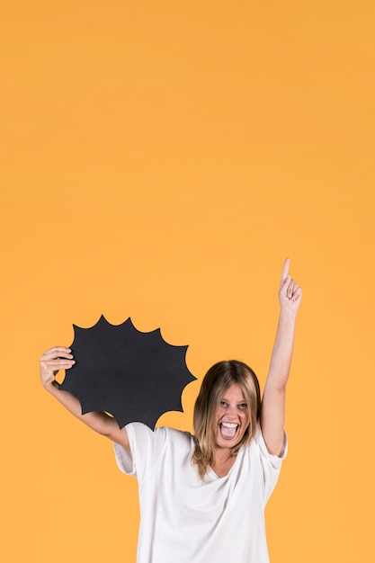 Young happy woman with mouth open holding black speech bubble and pointing up Free Photo