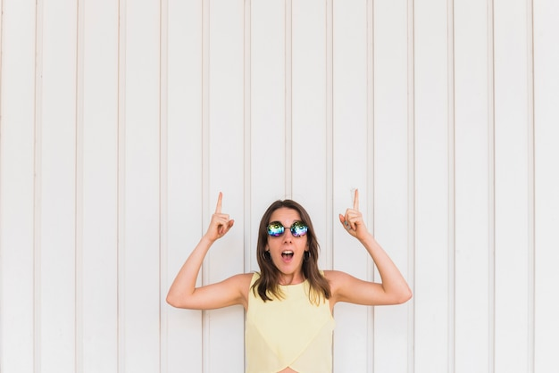 Young happy woman with thumbs up posing on white background Free Photo
