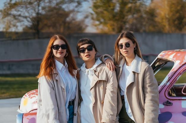 Giovani donne felici con borse della spesa in posa vicino a una vecchia automobile decorata Foto Gratuite
