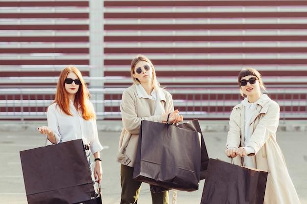 通りを歩いて買い物袋を持つ若い幸せな女性。 無料写真