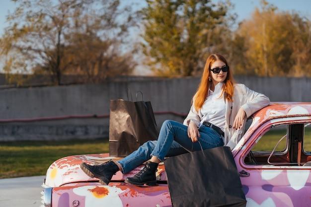 거리에 걷는 쇼핑 가방과 함께 젊은 행복 한 여자. 무료 사진