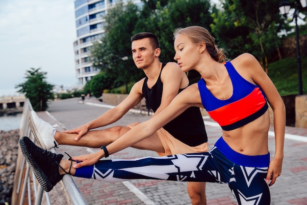 Young healthy couple doing sports exercises for legs, wearing sportswear, workout outdoors Free Photo
