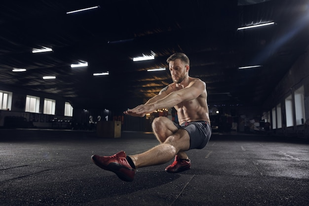 Young healthy man, athlete doing balance exercises, squats in gym. single model practicing hard, training his lower body. concept of healthy lifestyle, sport, fitness, bodybuilding, wellbeing. Free Photo