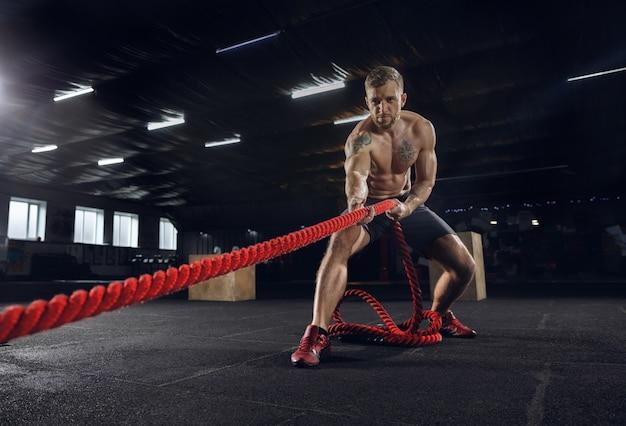 Молодой здоровый человек, спортсмен делает упражнения с веревками в тренажерном зале. одноместный манекенщиком практикующих жесткий и обучение его верхней части тела. концепция здорового образа жизни, спорта, фитнеса, бодибилдинга, благополучия. Бесплатные Фотографии
