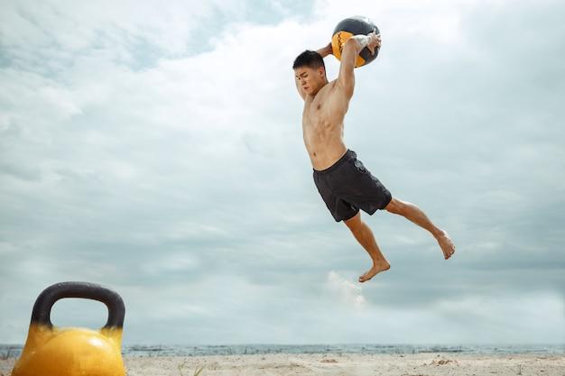 Atleta giovane uomo in buona salute facendo esercizio con il peso e la palla in spiaggia. formazione senza camicia modello maschile signle sul lato del fiume. concetto di stile di vita sano, sport, fitness, bodybuilding. Foto Gratuite
