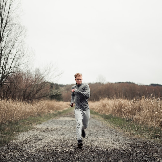 Young healthy man running on the dirt road Free Photo