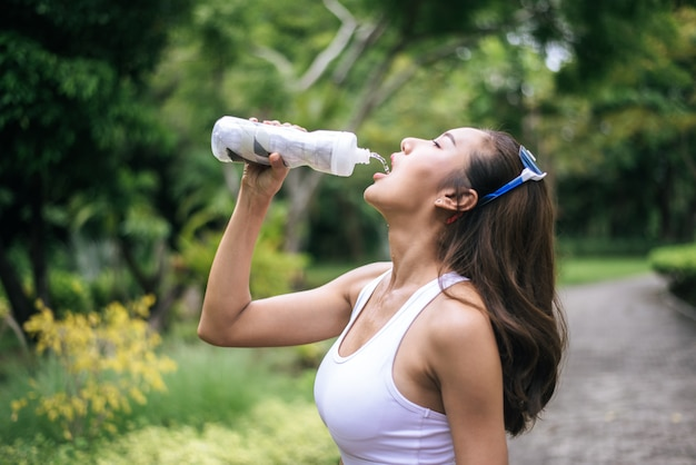 Free Photo | Young healthy woman drinking water from plastic bottles after jogging.