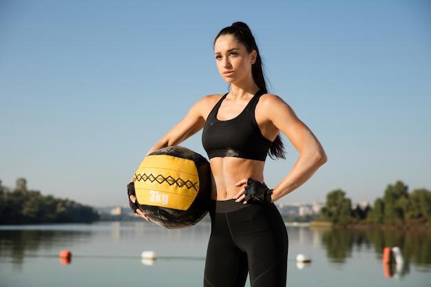 Giovane donna in buona salute in posa fiducioso con la palla in spiaggia. Foto Gratuite