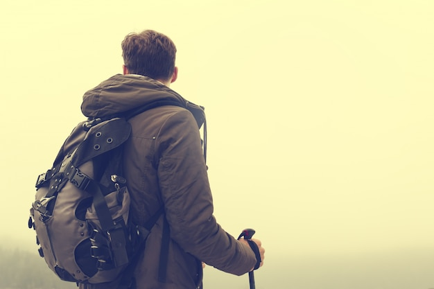 Young hiking man sportsman or traveler with backpack staying and looking on horizon. Toning.