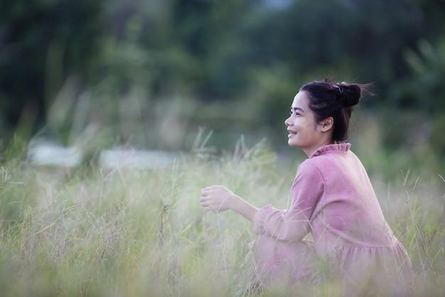 Молодая девушка хиппи, сидя в поле. Бесплатные Фотографии