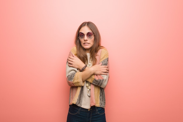 Young hippie woman on pink background going cold due to low temperature Premium Photo