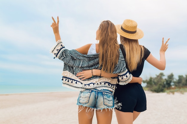 Young hipster beautiful women on vacation on tropical beach, stylish summer outfit, happy, fashion trend, hippie style, trendy accessories, girls friends together, positive mood, view from back Free Photo