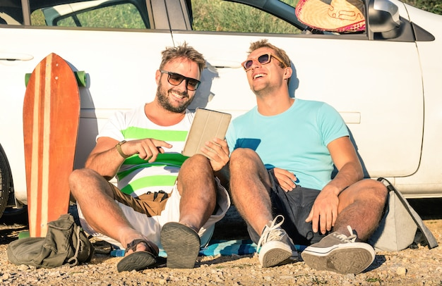 Young hipster best friends having fun with tablet during car roadtrip Premium Photo