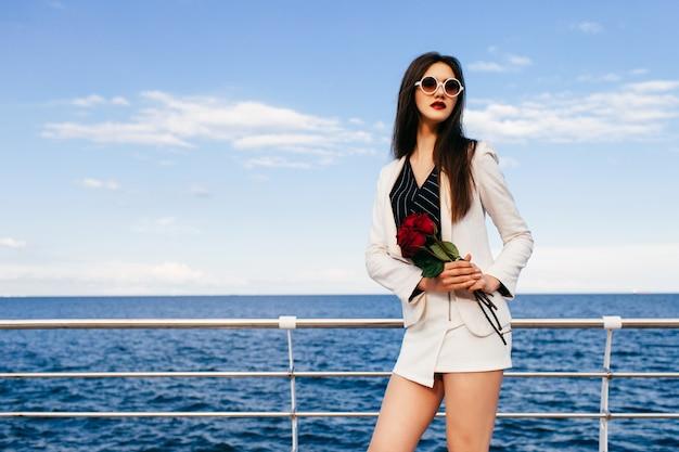 バラの小さな赤い花束と堤防でポーズをとって若い流行に敏感なブルネットの女性 無料写真