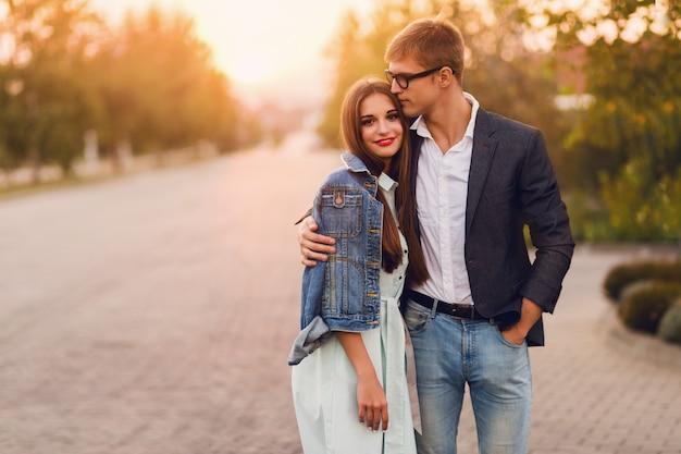 Молодая пара битник в любви открытый. сногсшибательный чувственный портрет молодой стильной пары моды представляя в заходе солнца лета. хорошенькая молодая девушка в джинсовой куртке и ее красивый парень пешком. Бесплатные Фотографии