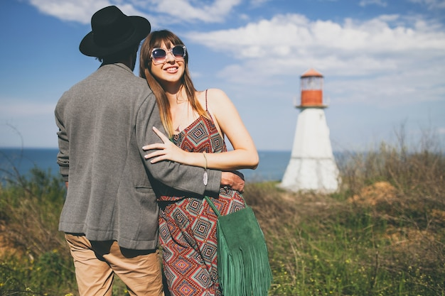 Young hipster couple indie style in love walking in countryside, lighthouse on background Free Photo