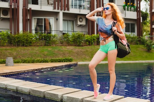 ジムに行く若い流行に敏感な生姜スリムな女性、カラフルな赤い髪、青いサングラス、スポーツスタイル、そばかす、あざ、バックパック、幸せ、遊び心、クールな服装、笑顔、官能的、運動、フィットネスアパレル 無料写真