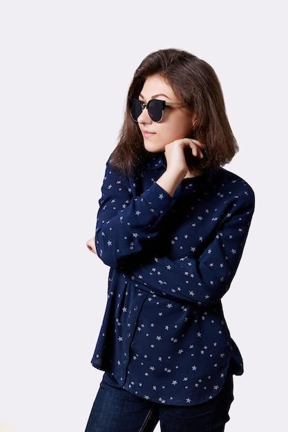 Una ragazza giovane hipster vestita in elegante camicia e jeans rotondi occhiali da sole tenendo la mano sotto il mento alla ricerca seria ed elegante. persone, stile di vita, moda e bellezza Foto Gratuite
