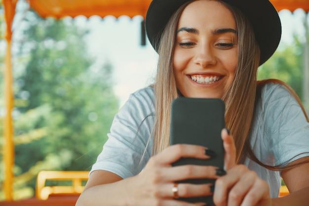 Молодая хипстерская девочка в модной шляпе, держащей смартфон в руках Бесплатные Фотографии