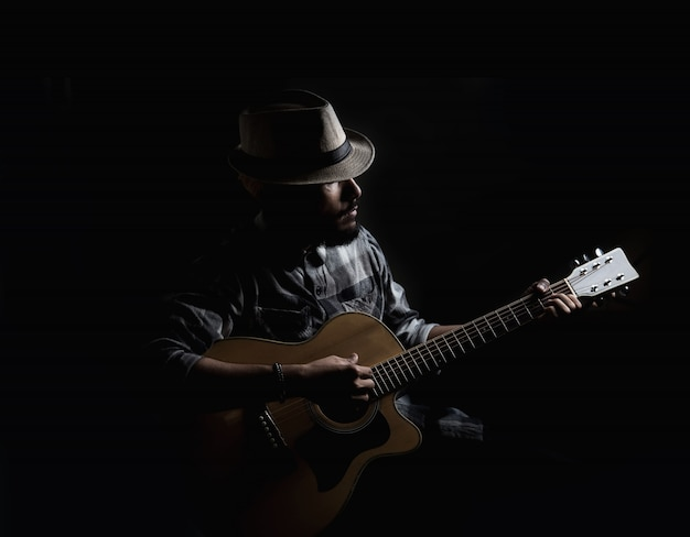 Young hipster guitarist play on the acoustic guitar . Free Photo