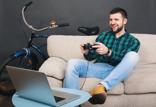 流行に敏感な若いハンサムなひげを生やした男が自宅のソファに座って、ノートブックでビデオゲームをプレイ 無料写真