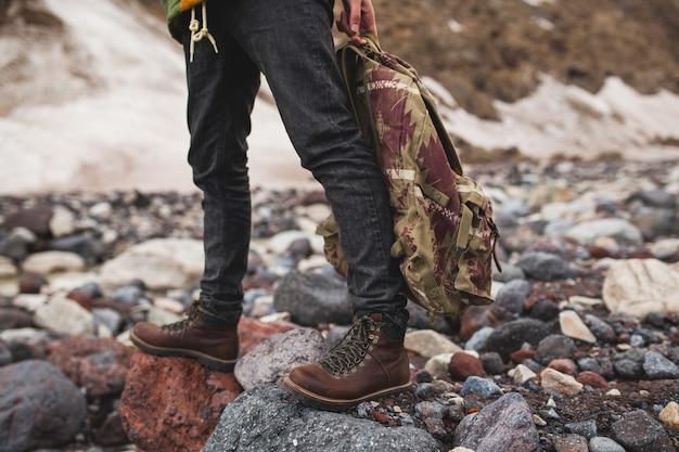 流行に敏感な若い男、川でのハイキング、野生の自然、冬休み、バックパックを手で押し、詳細を閉じる 無料写真