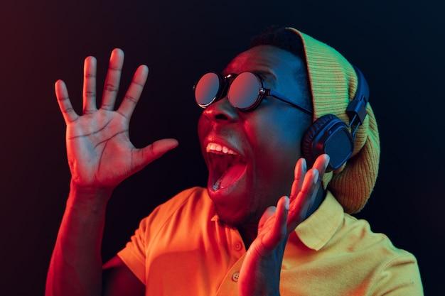 ネオンライト付きの黒いスタジオでヘッドフォンで音楽を聴いている若い流行に敏感な男。 無料写真