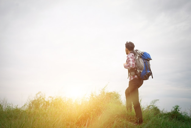 Young hipster man outdoor with backpack on his shoulder, time to Free Photo