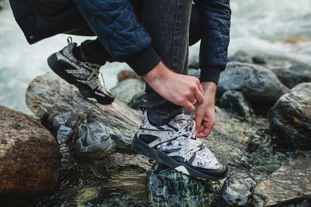 冬の森の川の岩の上を歩く流行に敏感な若い男 無料写真