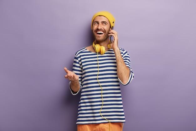 Il giovane hipster parla casualmente con un amico tramite smartphone, discute di qualcosa di divertente accaduto con lui, ha un'espressione felice del viso, indossa abiti eleganti, ascolta musica in cuffia. comunicazione Foto Gratuite