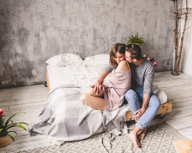 Young hipster with beard and attractive woman resting at home while sitting on bed at home Premium Photo