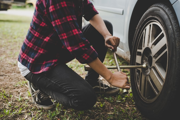 Young hipster woman checking out a flat tyre on her car try to fix. Free Photo