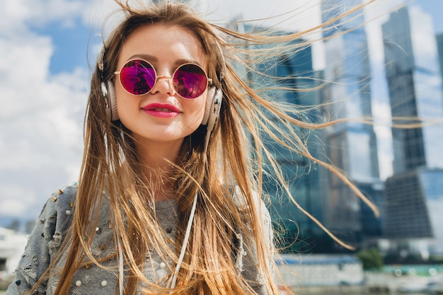ピンクのサングラスをかけているヘッドフォンで音楽を聞いて通りで楽しんでいる流行に敏感な若い女性 無料写真