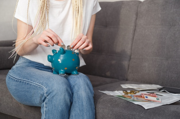 自宅のソファに座って旅行のために貯金箱にコインを入れている若い流行に敏感な女性。貯蓄の概念 Premium写真