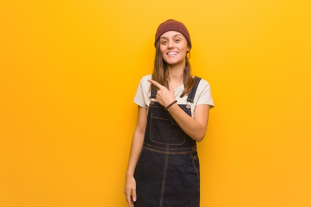 Young hipster woman smiling and pointing to the side Premium Photo