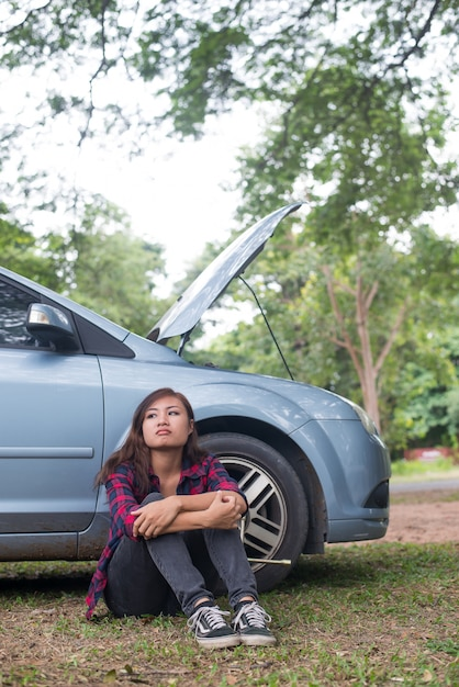 Young hipster woman waiting for roadside assistance after her car breaks down at the side of the road sitting against her car. Free Photo