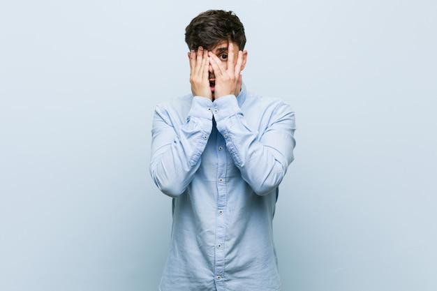 Молодой испаноязычный деловой человек моргает сквозь пальцы испуганно и нервно. Premium Фотографии