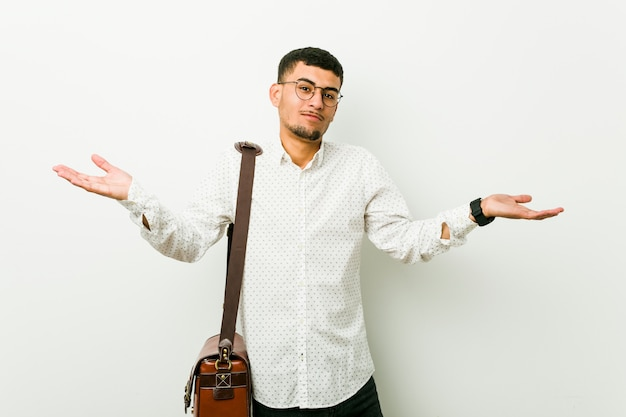 Young hispanic casual business man doubting and shrugging shoulders in questioning gesture. Premium Photo