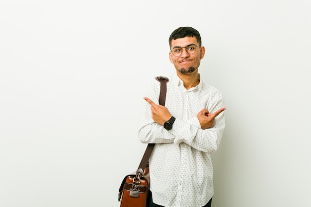 Young hispanic casual business man points sideways, is trying to choose between two options. Premium Photo