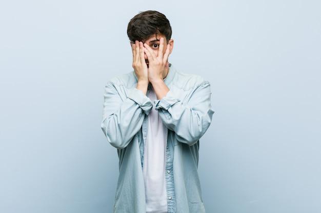 Молодой латиноамериканский классный человек моргает сквозь пальцы испуганно и нервно. Premium Фотографии