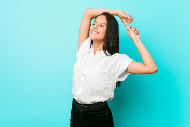 Young hispanic cool woman against a blue wall stretching arms, relaxed position. Premium Photo