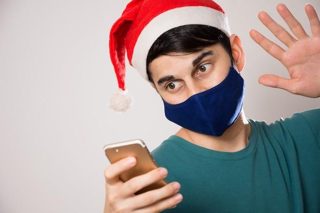 Молодой латиноамериканец с маской для лица и приветствием в шляпе санты во время видеозвонка Бесплатные Фотографии