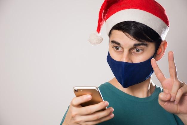 Молодой латиноамериканский мужчина с маской и шляпой санты смотрит в свой телефон и делает жест мира Бесплатные Фотографии
