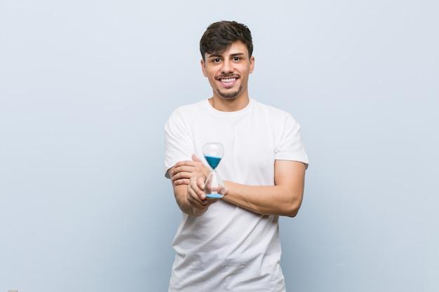 組んだ腕に自信を持って笑みを浮かべて砂時計を持って若いヒスパニック男。 Premium写真