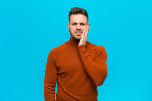 Young hispanic man holding cheek and suffering painful toothache, feeling ill, miserable and unhappy, looking for a dentist against blue wall Premium Photo