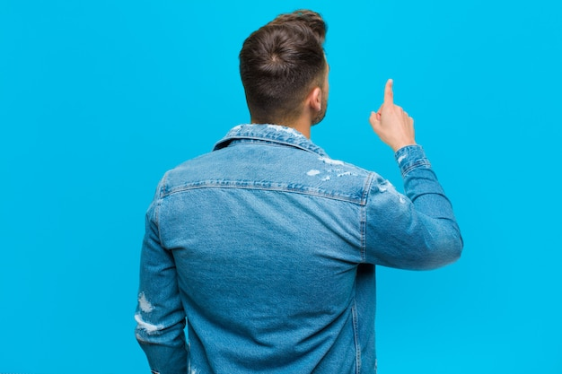 Young hispanic man standing and pointing to object on copy space, rear view against blue wall Premium Photo
